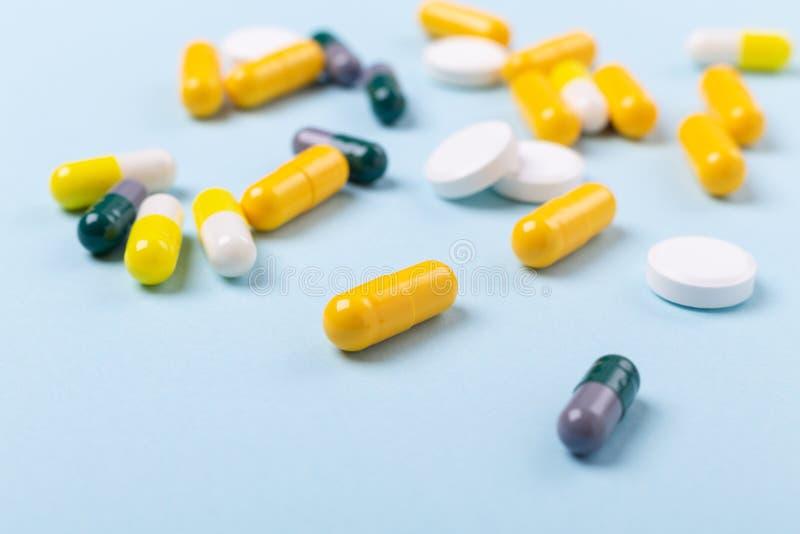 多色片剂和药片胶囊在蓝色背景特写镜头 免版税库存图片