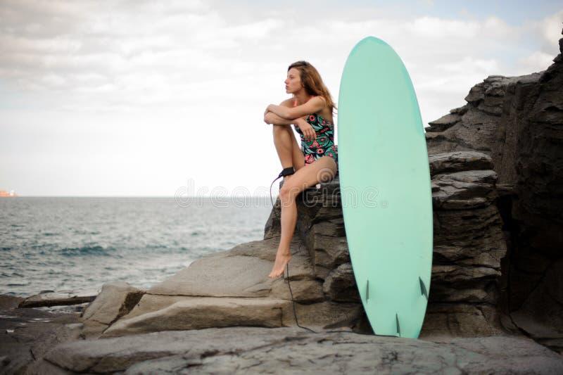 多色的泳装的美女在海浪附近坐岩石 图库摄影