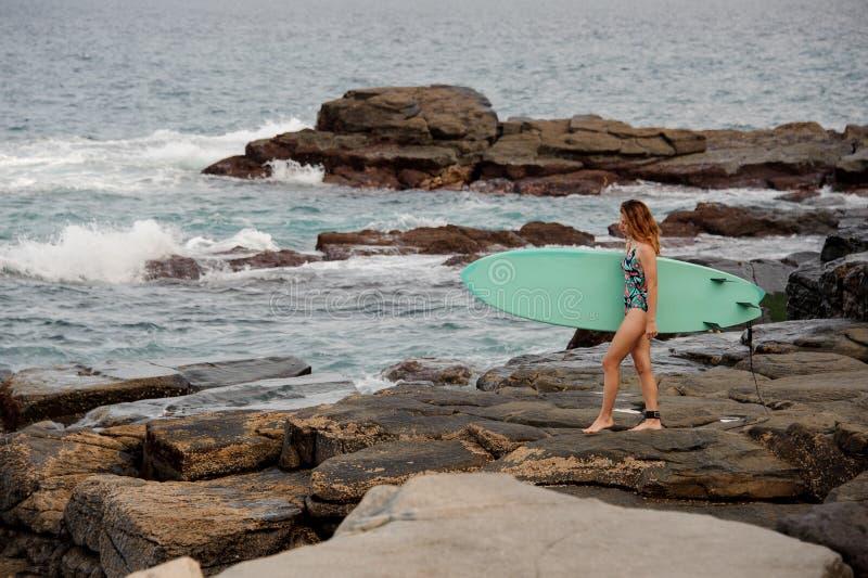多色的泳装的运动的女孩走与在岩石的海浪的在海滩 库存图片