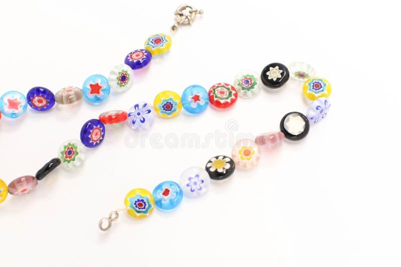 多色的首饰成串珠状在白色背景的五颜六色的装饰物项链 库存照片