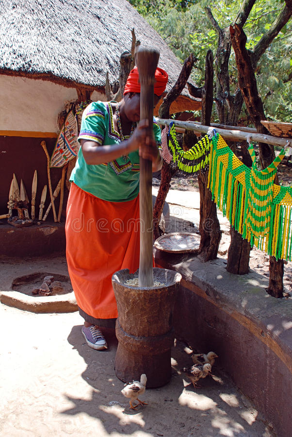 多色礼服的非洲妇女烹调玉米膳食的 库存图片