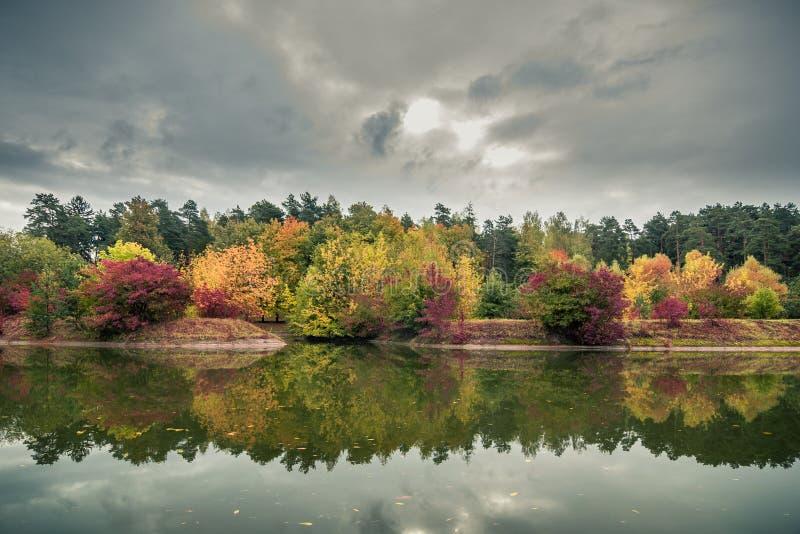 多色秋天风景 公园的美丽的景色river'的;s海岸在多云天气的剧烈的天空下 免版税库存图片