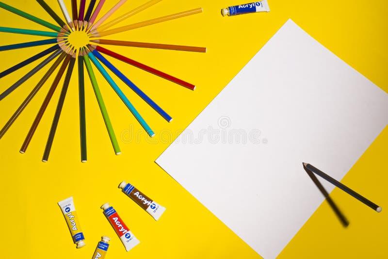 多色铅笔和纸片在黄色背景的 艺术和创造性概念 图库摄影