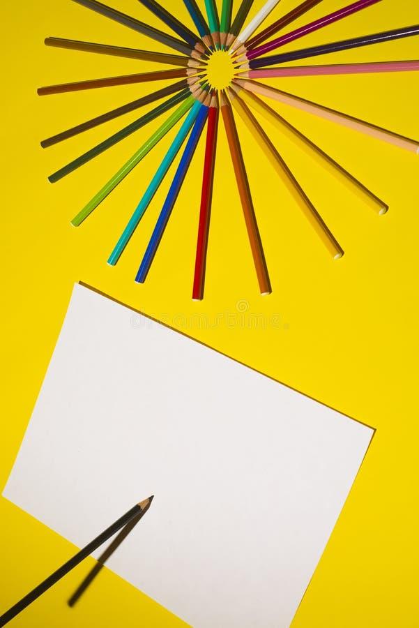 多色铅笔和纸片在黄色背景的 艺术和创造性概念 免版税库存图片