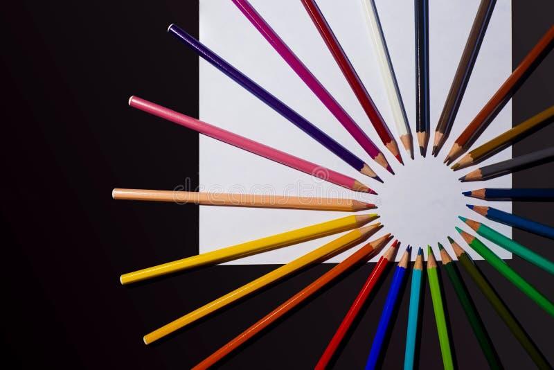 多色铅笔和纸片在黑背景的 艺术和创造性概念 免版税图库摄影