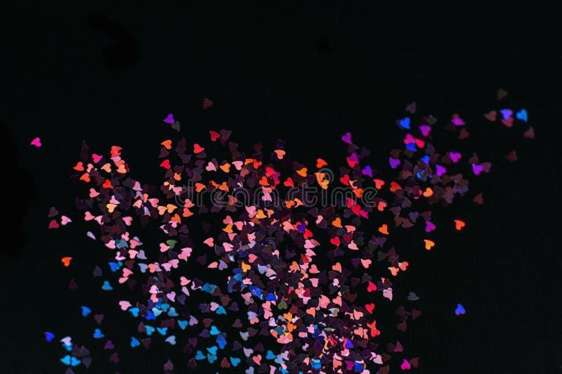 多色bokeh光,在黑背景的微小的心脏,顶视图、狂欢节、夜党邀请或者欢乐背景, 库存照片