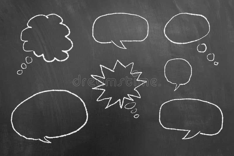 多讲话起泡在黑板或黑板的图画 免版税库存照片