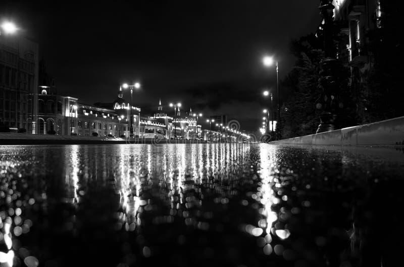 多雨夜在巴库市,汽车车灯通过看法的薄雾关闭发光从界线, selec的水平 免版税库存照片