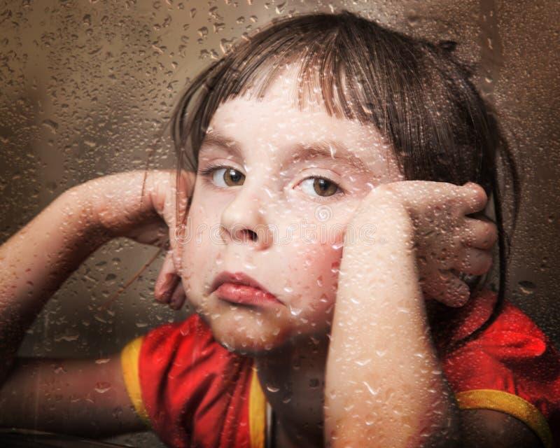 多雨窗口的哀伤的孩子 免版税库存照片