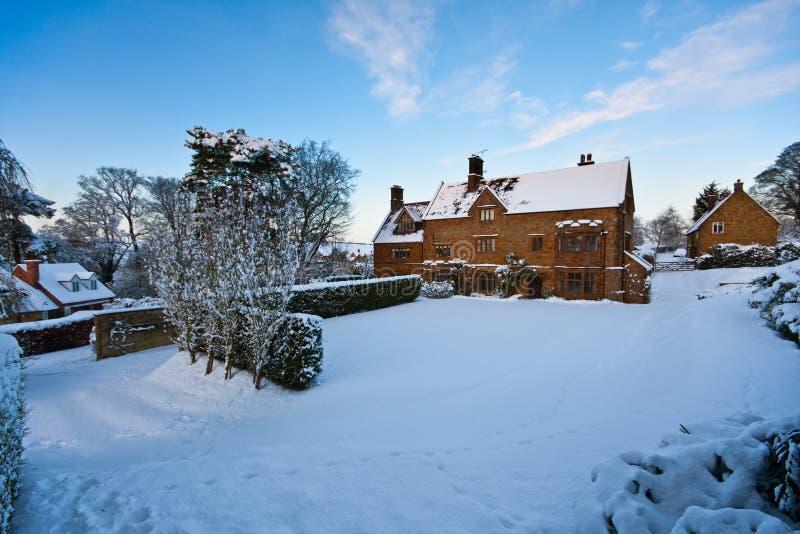 多雪下午明亮的农庄的房子 库存图片