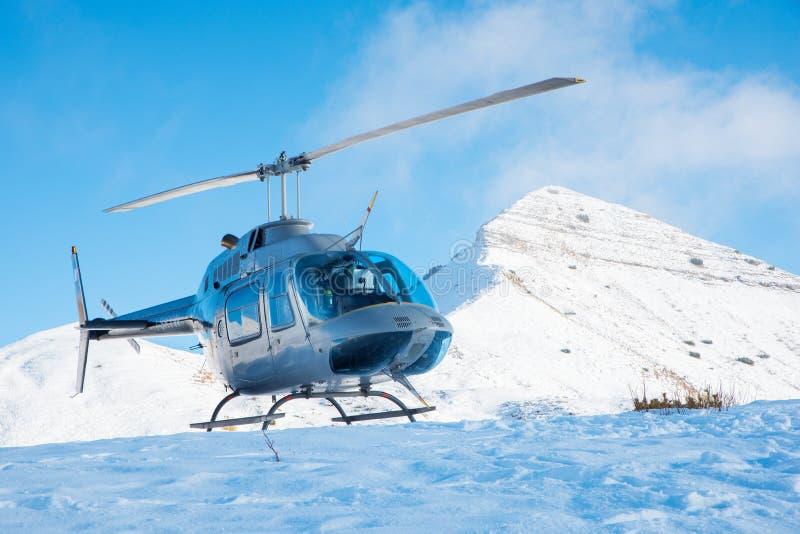 多雪的表面上的直升机着陆在山 库存图片