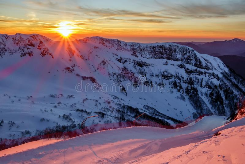 多雪的高加索山脉美好的风景冬天山日落风景和高尔基Gorod山滑雪胜地滑雪倾斜  库存照片