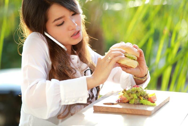多任务妇女谈话在电话,当吃汉堡时 库存照片