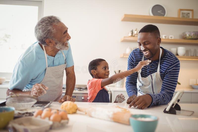 多代的家庭用在站立在厨房里的鼻子的面粉 库存图片