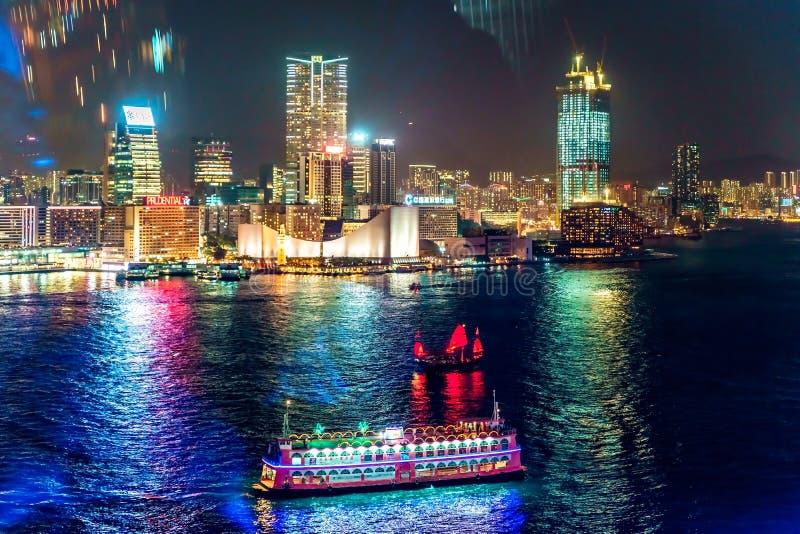 夜与城市光的香港都市风景和从观察观看的巡航小船在维多利亚港口江边转动 免版税库存照片