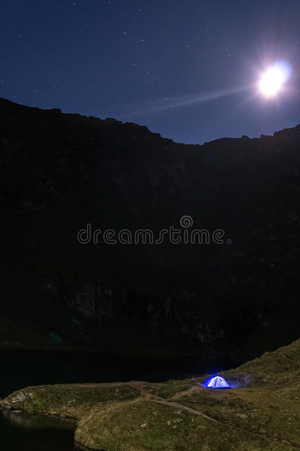 夜与有启发性蓝色帐篷的山风景 山峰和月亮 室外在Lacul Balea湖,Transfagarasan, 库存图片