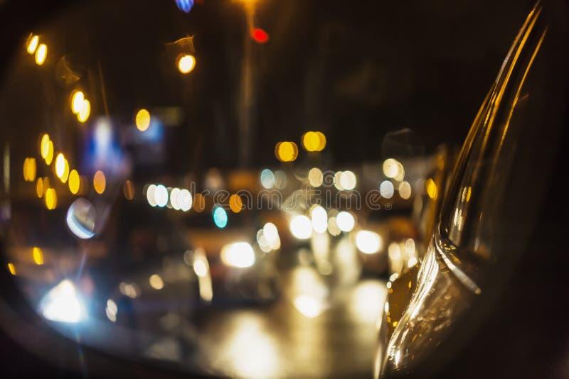 夜与汽车的城市交通果酱抽象背景通过汽车镜子点燃 免版税库存照片