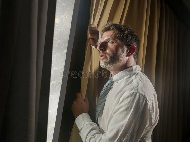 夜光运作晚看的商人办公室画象通过周道的窗口和哀伤沉思的感觉担心和 免版税库存照片