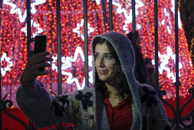 夜圣诞节的妇女使用智能手机屏幕采取 免版税库存照片