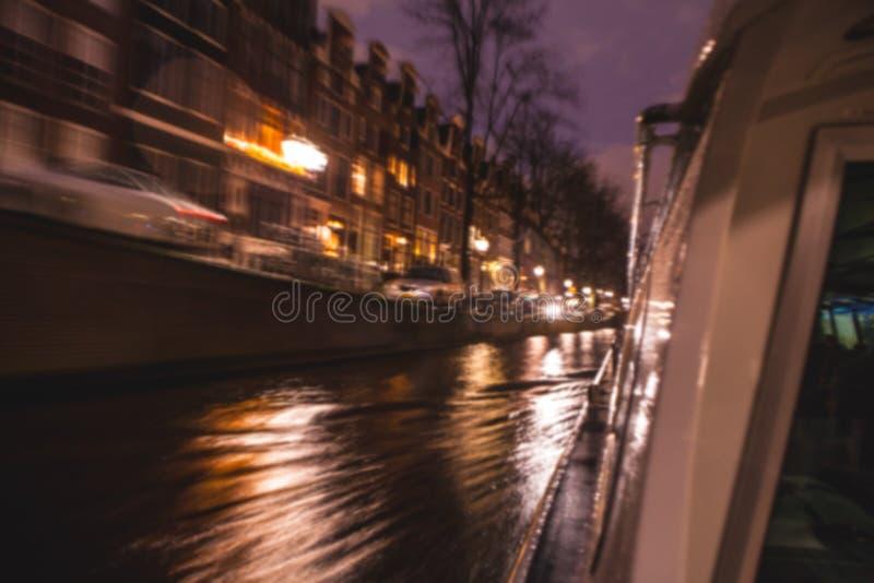 夜在阿姆斯特丹渠道的照明设备反射从移动的巡航小船 作为背景的被弄脏的抽象照片 图库摄影