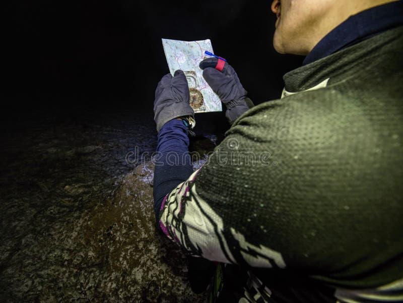 夜在黑黄色红色球衣举行纸地图的鞭尾蜥 库存照片