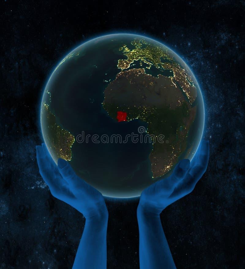 夜地球上的象牙海岸在空间的手上 向量例证