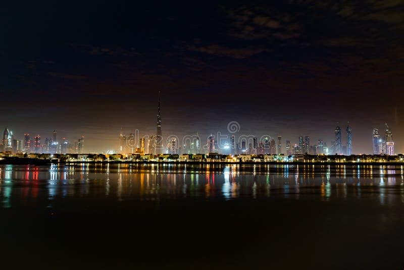 夜城市光或黄昏的迪拜 在哈里发塔的黎明 每夜的迪拜街市 看法从海到迪拜码头 免版税库存图片