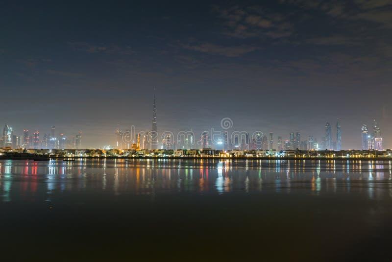 夜城市光或黄昏的迪拜 在哈里发塔的黎明 每夜的迪拜街市 看法从海到迪拜码头 免版税库存照片