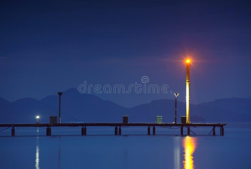 夜射击了有码头和灯塔的小游艇船坞 免版税库存图片