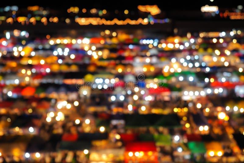 夜市高视图抽象迷离bokeh背景从建立五颜六色的帐篷零售店和照明设备的在Rachada雨 免版税库存照片