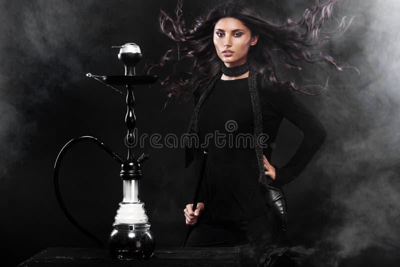 夜总会或酒吧烟的年轻,美丽的妇女水烟筒或shisha 乐趣抽烟 性感的烟 库存照片
