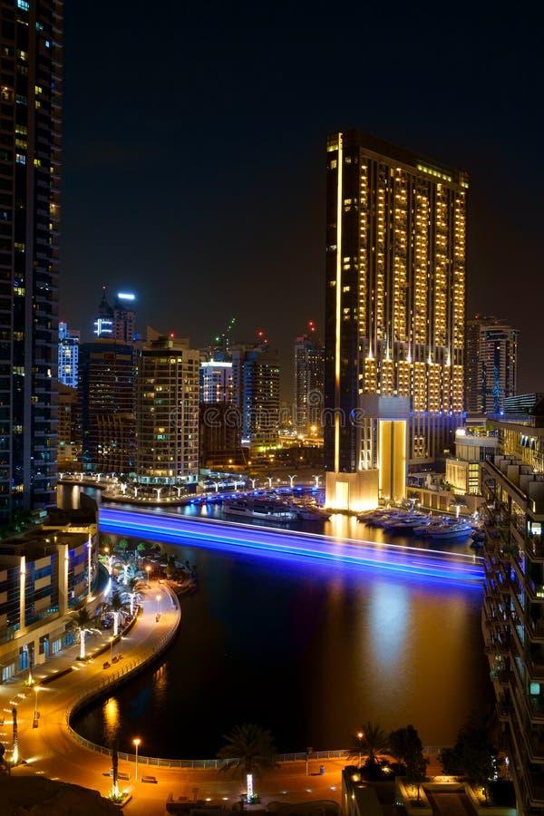 夜河交通长的追踪者在迪拜阿拉伯联合酋长国沿有五颜六色的反射和被弄脏的smok的一条城市河集中 免版税库存图片