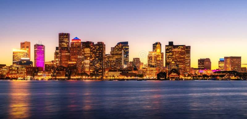 夜波士顿市地平线的都市风景照片与日落在波士顿港口 免版税库存照片