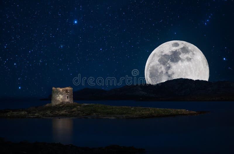夜海景在有塔的撒丁岛在La Pelosa海滩的海岸,在斯廷廷奥,有满天星斗的天空和超级月亮的 免版税库存图片