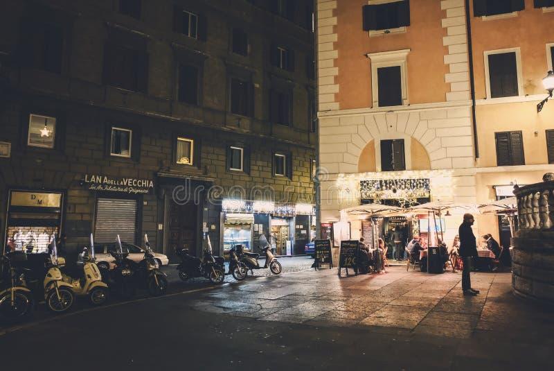 夜生活在罗马 餐馆和许多滑行车的人们在街道上停放了 免版税图库摄影