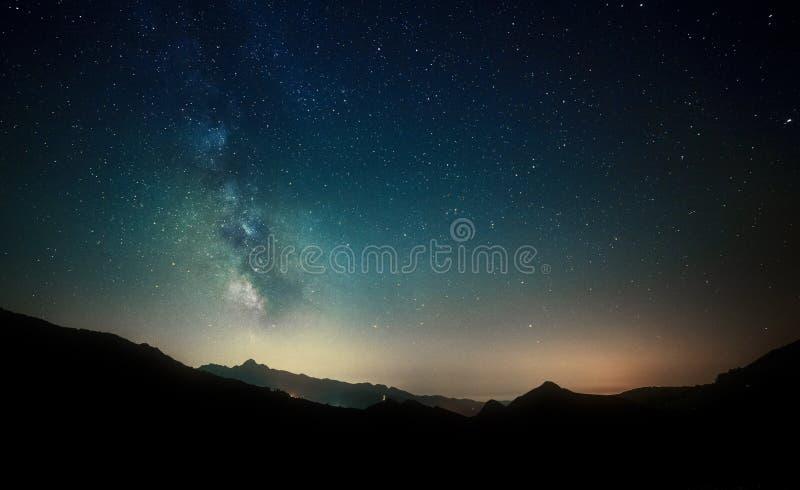 夜空担任主角与在山背景的银河 免版税图库摄影