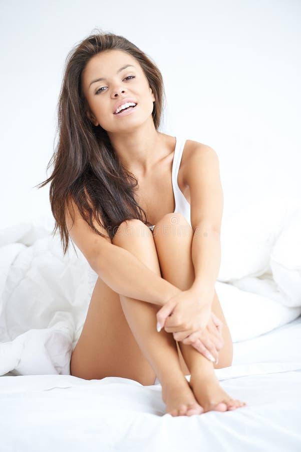 夜穿戴的少妇坐白色床 免版税库存照片
