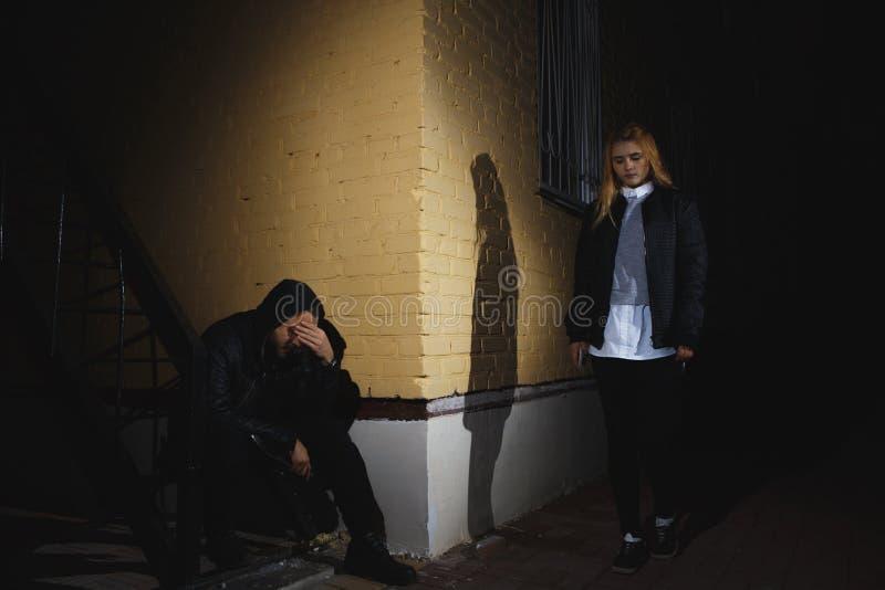 夜街道盗案场面:拿走年轻女性袋子的人 免版税库存照片