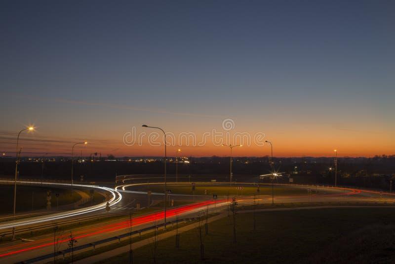 夜视图与不可思议的日落的街道追踪者在拉脱维亚陶格夫匹尔斯市 图库摄影