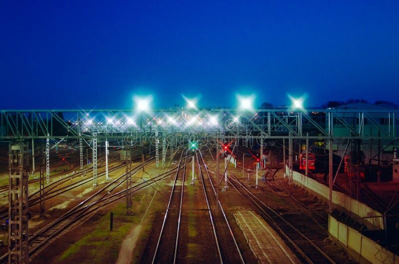 夜视图从上面在铁路 商品火车、货物无盖货车和储水池 库存图片