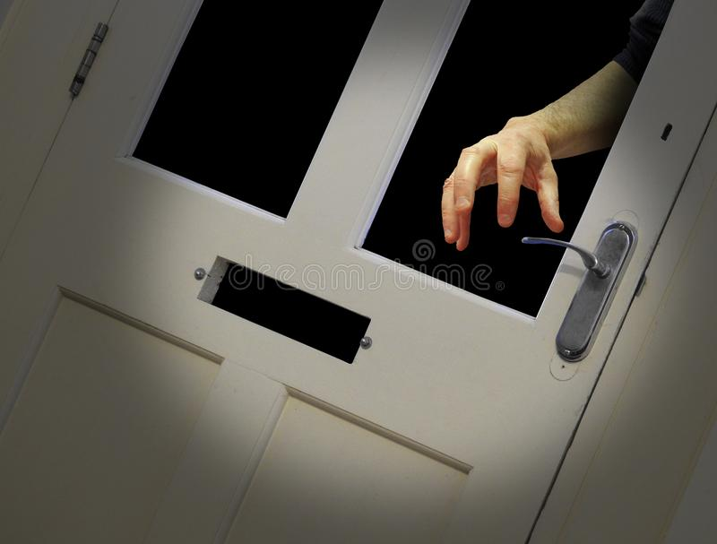 夜贼手通过残破的玻璃门 库存图片
