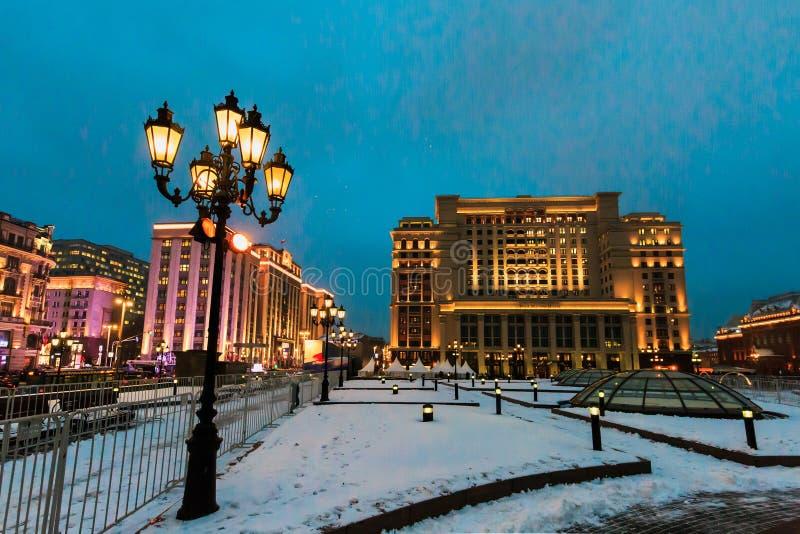夜都市风景、旅馆`四个季节`和杜马,街灯和雪在Manezhnaya在冬天摆正 莫斯科俄国 免版税库存图片