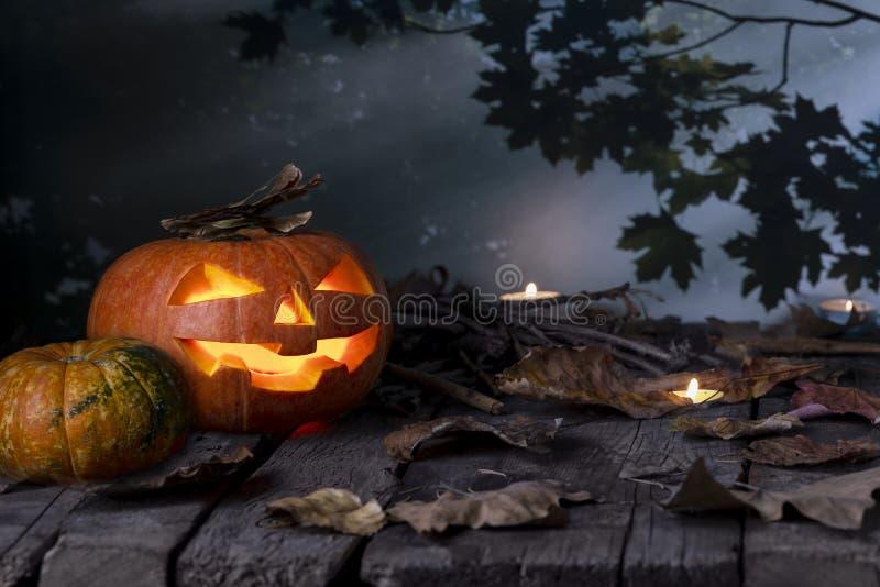 夜里神秘森林里木桌背景的万圣节南瓜头灯和蜡烛 图库摄影