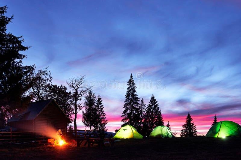 夜野营 游人有休息在营火近充分有启发性帐篷和木房子在惊人的夜空下  免版税图库摄影