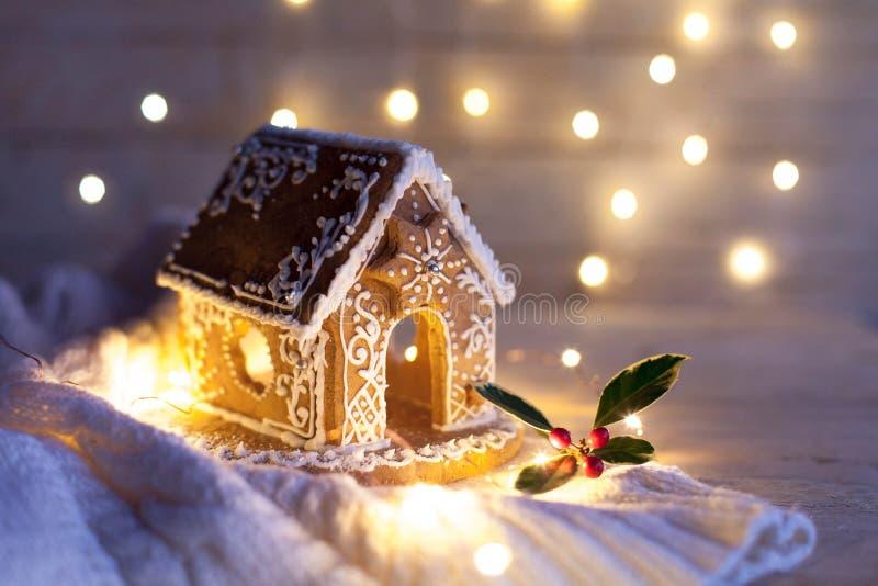 夜间圣诞姜饼屋,木质和针织背景的舒适装饰 免版税库存照片