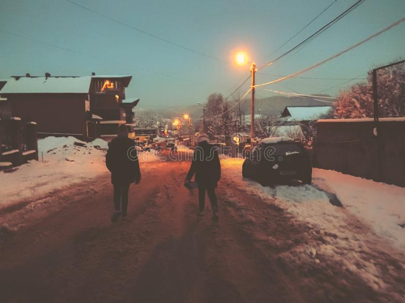 夜间山s日落ural冬天 孩子在雪走 村庄在一个多雪的晚上 山滑雪场巴库里阿尼 库存图片