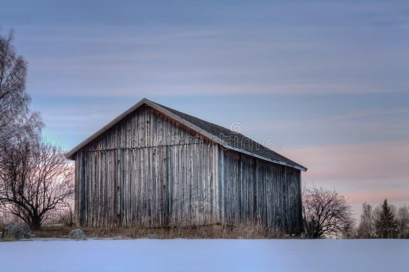 夜间日落的灰色老谷仓 库存照片