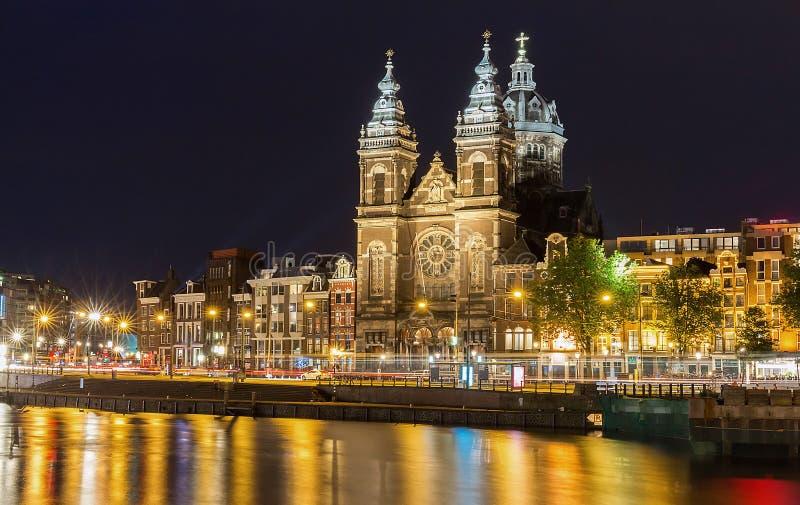 夜阿姆斯特丹圣尼古拉,荷兰,荷兰运河和大教堂城市视图  库存图片