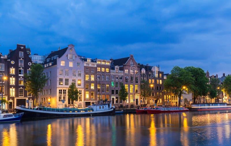 夜阿姆斯特丹运河、典型的荷兰房子和小船,荷兰,荷兰城市视图  免版税库存照片