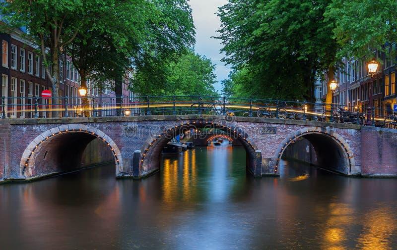 夜阿姆斯特丹运河和七座桥梁,荷兰城市视图  免版税库存图片